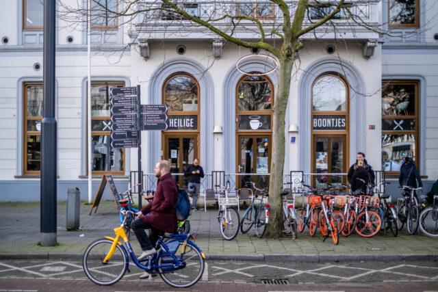 Fietser op OV fiets bij Heilige Boontjes Rotterdam met deelfietsen op achtergrond